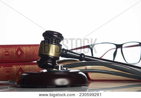 Medicine Law Concept. Law Books With Wooden Judges Gavel And Medical Stethoscope On White Table In A