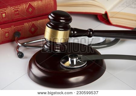 Judges Gavel  With Law Books And Medical Stethoscope On White Table In A Courtroom Or Enforcement Of