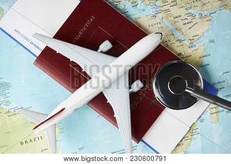 Boarding Pass And A Passport Travel Documents With Medical Stethoscope And Airplane On World Map Bac