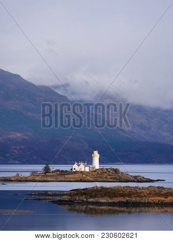 Famous Isle Ornsay With  Lighthouse Tower, Isle Of Skye, Scotland, Uk. Snowy Mountains In Background