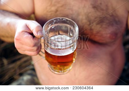 A Glass Of Beer Is Held By A Fat Man In Hand. A Glass Of Beer Near A Large Beer Belly Of A Man, Clos