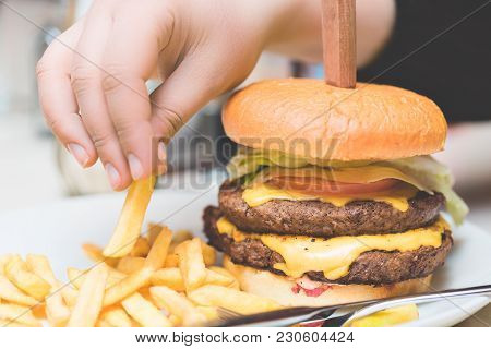 Fast Food Concept. Female Hand Taking French Fries Near Big Fresh Burger. Close Up Image.