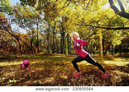 Healthy Athletic Woman Training With Suspension Straps In Park