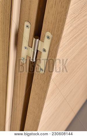 Closeup Of Metal Hinges On Light Brown Wooden Doors