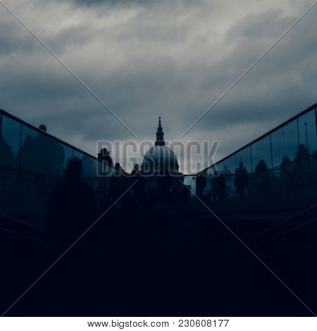 Long Exposure Of Pedestrians At London, England, Uk Millenium Bridge With St. Paul's Cathedral In Ba