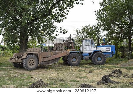 A Large Tractor With A Grader On The Trailer. Agricultural Machinery.