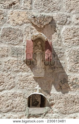 A Very Old Stone Carved Art Sculpture Of Virgin Mary With Child. In A Niche Below A Picture Of Virgi