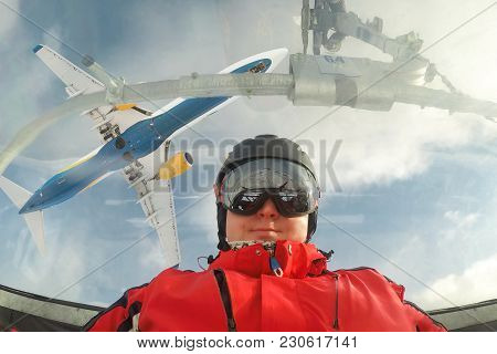 Man Skier Wearing Goggles And Helmet With Biohazard Sign Making Selfie While Sitting In A Ski Lift C