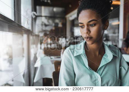 Portrait Of A Young Beautiful Brazilian Girl Sitting In The Cafe And Wistfully Looking Aside; A Char