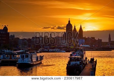 Amsterdam cityscape skyline with Church of Saint Nicholas (Sint-Nicolaaskerk) and boats on the pier on sunset with dramatic sky. Amsterdam, Netherlands