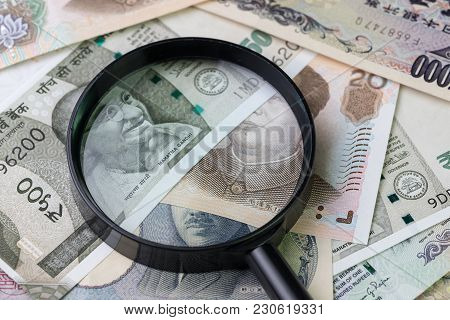 Magnifying Glass On Pile Of Asian Leading Country New Emerging Market Money Banknotes, Indian Rupee,