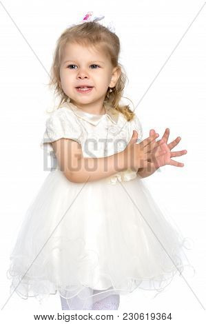 A Beautiful Little Girl Claps Her Hands. Concept Of Happy Childhood, Harmonious Development Of A Chi