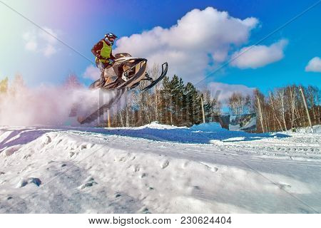 Sport Yellow Snowmobile Jump. Cloud Of Snow Dust From Under Snowmobile Tracks. Concept Quick Movemen