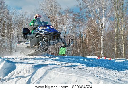 Sport Blue Snowmobile Jump. Sunny Winter Day With Blue Sky. Concept Quick Movement. Copy Space.