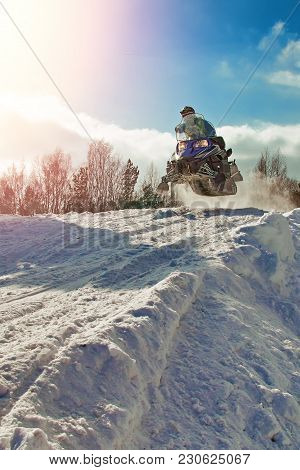 Sport Blue Snowmobile Jump. Clear Sunny Winter Day. Concept Quick Movement. Extreme Sport Background