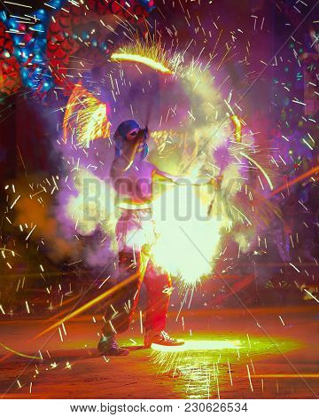 Nakhon Sawan, Thailand - Feb 19, 2018: A Fire Artist Spins His Fire Torches Scattering Flames And Sp