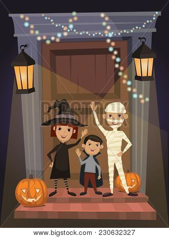 Children In Vampire Costumes, Witches And Mummies Stand On Threshold Of The House On The Halloween N