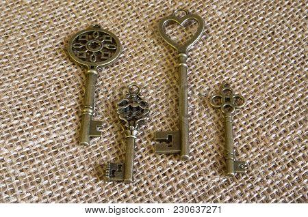 Four Bronze Ancient Keys On Burlap. Vintage Ornament. Horizontal Format. Indoors. Color. Photo.