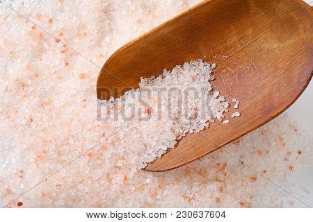 scoop of coarse grained salt on coarse grained salt background