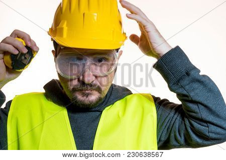 hobby a man who wants to do a work without knowledge, work without experience. Do it yourself, man dressed in yellow builder helmet with protective glasses ready to start the construction work