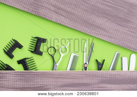 Scissors, Combs, Hair Clippers, Composition On A Green Background, Place For Writing On A Brown Boar