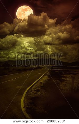Beautiful Landscape Of Dark Sky With Bright Full Moon Behind Clouds And Asphalt Roadway Through Subu
