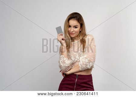 Young Attractive Girl Looks Impressively At The Camera, Holding A Plastic Credit Bank Card In Front