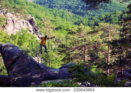 A Man Is Jumping On Top Of A Mountain.