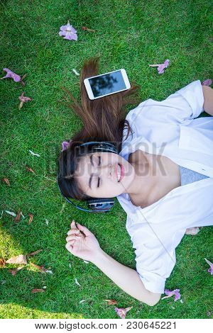 Young Woman Lying On Grass Floor Listening Music From Moblie Phone With Headset. Girl Chilling Lifes