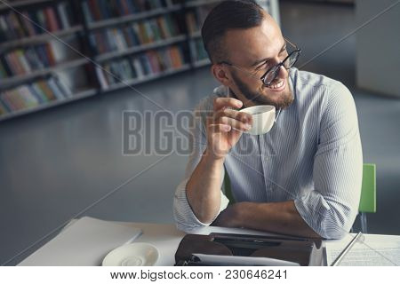 Young writer with a cup of coffee in library