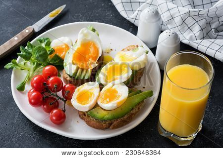 Avocado And Poached Egg Toasts, Salad And Orange Juice On Stone Table. Closeup View