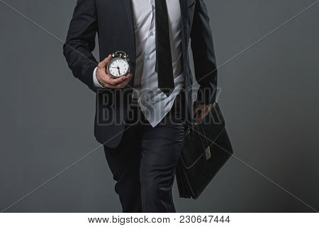 Close Up Of Untidy Tardy Businessman. Shirt Jerked From Trousers. He Carrying Alarm Clock And Briefc
