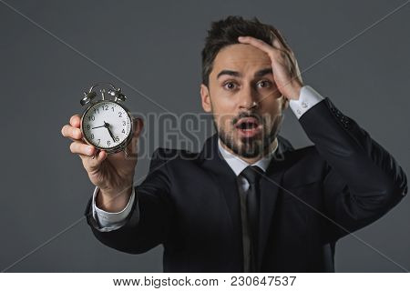 Waist Up Portrait Of Scared And Discouraged Man Clutching Head And Showing Time At Snooze. Focus On