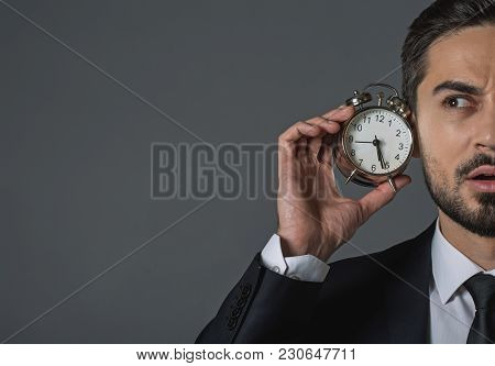 Close Up Half Face Of Attentive Handsome Man Holding Snooze In Hand And Listening Wake-up Call. Isol
