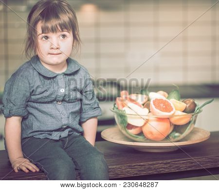 Little Cute Thoughtful Girl Sitting Near A Plate With Fruit On A Kitchen Table, Concept Of A Healthy