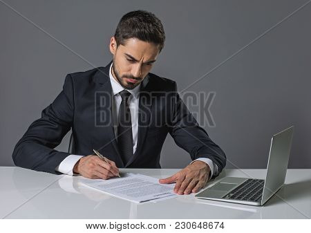 Young Concentrated Bearded Man Sitting At The Table And Reading Agreement. Copy Space In Right Side