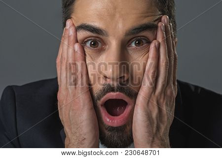 In Mute Amazement. Close Up Portrait Of Shocked Bearded Man Clasping Head, Staring With Astonishment