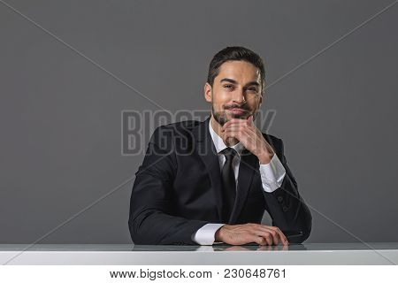 Waist Up Portrait Of Cheerful Bearded Man. He Is Sitting At The Table With Chin Propped In Hand And