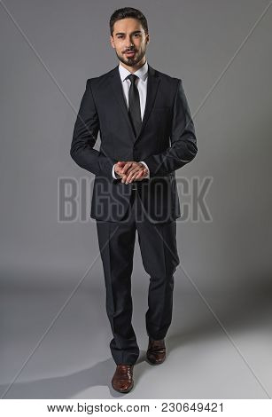 Full Length Portrait Of Smiling And Pensive Handsome Man In Business Suit, Folding Arms. He Is Looki