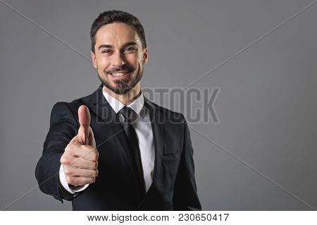 It Is Great. Waist Up Portrait Of Standing Young Smiling Businessman Showing Ok Sign. Isolated On Gr