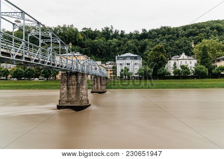 Salzburg, Austria - August 6, 2017: Steel Bridge Over River In Salzburg A Cloudy Day. Long Exposure