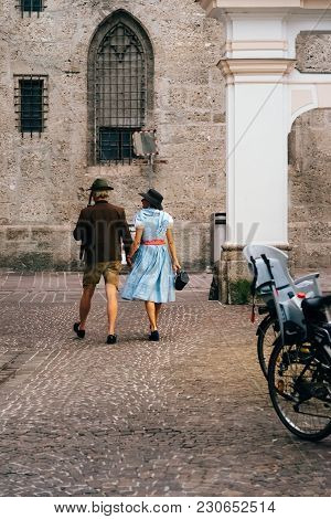 Salzburg, Austria - August 6, 2017: Couple Dressed In Traditional Clothes Walking On Historic City C