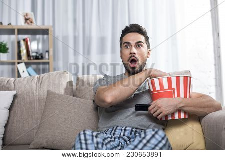 Waist Up Portrait Of Astonished Guy Sitting On Sofa Holding Bucket With Popcorn. Copy Space In Left