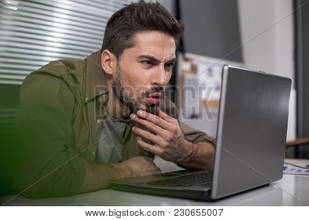 Dazed Bearded Guy Sitting At Table In His Workplace And Looking At Notebook Screen With Astonishment