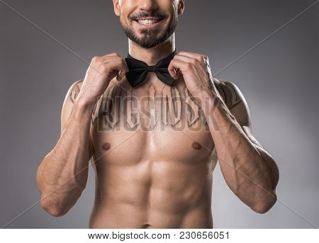 Smiling Elegant Guy With Naked Fit Body Straightening Bow Tie On His Neck. Isolated On Background