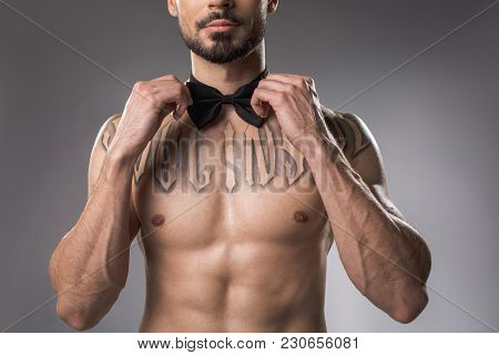Serene Muscular Gentleman Standing Topless And Wearing Bow Tie On His Neck. Isolated On Background