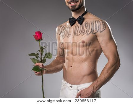 Cheerful Naked Man With Bow Tie On Neck Standing And Holding Flower In Hand. Isolated On Background