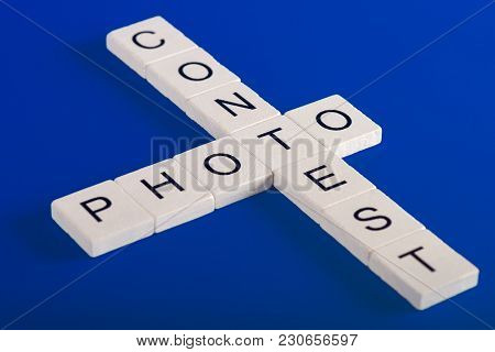 Photo Contest Phrase Made Of White Wooden Blocks On Blue Background In Crossword Style