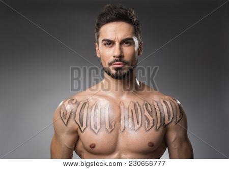 Portrait Of Attractive Bearded Man With Good Physique Staring With Gravity. Isolated On Background