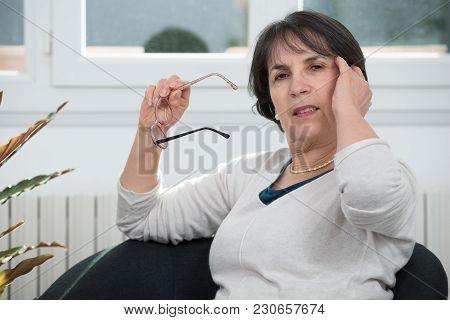 A Brunette Mature Woman Rubbing His Eyes